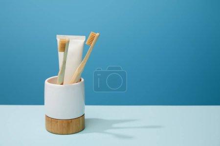 Photo pour Support avec dentifrice en tube et brosses à dents en bambou sur table et fond bleu - image libre de droit