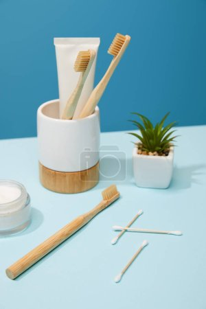 Photo pour Support avec dentifrice en tube et brosses à dents en bambou, crème cosmétique et plante en pot sur table et fond bleu - image libre de droit
