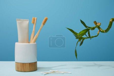 Photo pour Support avec brosses à dents, dentifrice en tube, bâtons d'oreille et tige de bambou vert sur table et fond bleu - image libre de droit
