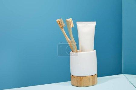 Photo pour Support avec brosses à dents en bambou, dentifrice en tube et miroir sur table et fond bleu - image libre de droit