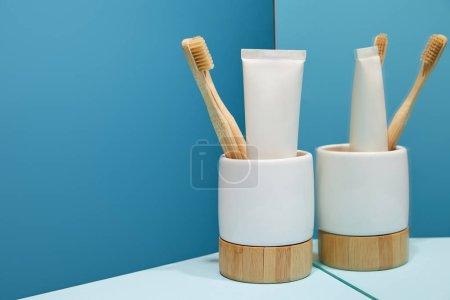 Photo pour Support avec brosses à dents en bambou, dentifrice en tube près du miroir sur table et fond bleu - image libre de droit