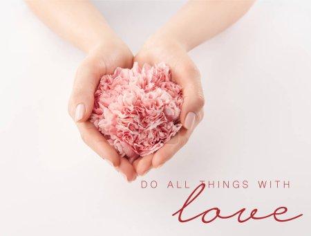 Photo pour Vue recadrée des mains féminines avec oeillets roses et faire toutes choses avec l'amour lettrage - image libre de droit