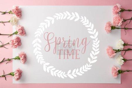 Photo pour Vue du dessus de belles fleurs d'oeillet rose et blanc et carte avec lettrage printanier dans un cadre rond sur fond rose - image libre de droit