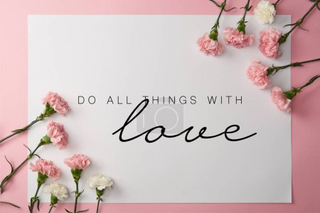 Photo for Top view of pink and white carnation flowers and card with do all things with love lettering on pink background - Royalty Free Image