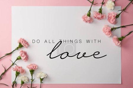 Photo pour Vue de dessus des fleurs d'oeillets roses et blancs et une carte avec faire toutes choses avec amour lettres sur fond rose - image libre de droit