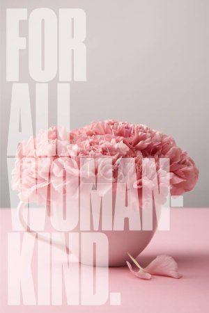 Photo for Pink carnation flowers in cup on grey background with for all woman kind lettering - Royalty Free Image
