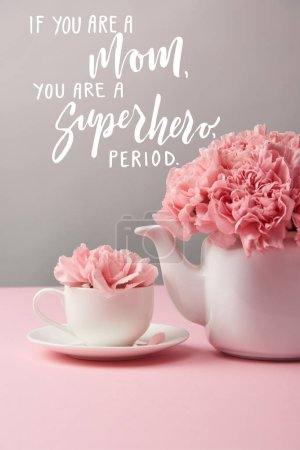 Photo for Pink carnation flowers in cup and teapot on grey background with if you are a mom, you are a superhero, period lettering - Royalty Free Image