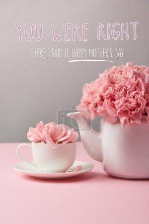 Photo pour Fleurs d'oeillets roses dans la tasse et théière sur fond gris avec le lettrage de jour de mères heureux - image libre de droit