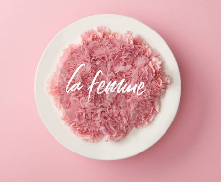 Photo for Top view of pink carnation flowers in white plate on pink background with la femme lettering - Royalty Free Image