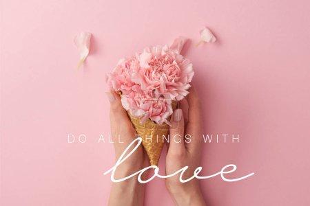Photo pour Recadrée vue de femme tenant roses fleurs d'oeillets en mains avec toutes choses avec amour illustration - image libre de droit
