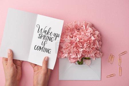 Photo pour Vue recadrée de la femme tenant la carte de vœux avec réveil, le printemps arrive lettrage près des fleurs d'oeillet dans une enveloppe sur fond rose - image libre de droit