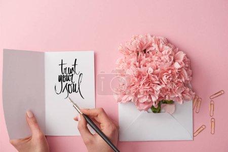 Photo pour Vue recadrée de femme tenant la carte de voeux avec confiance votre lettrage de l'âme et la plume près de fleurs d'oeillets en enveloppe sur fond rose - image libre de droit
