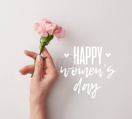 Photo for Partial view of woman holding pink carnation on grey background with happy womens day lettering - Royalty Free Image