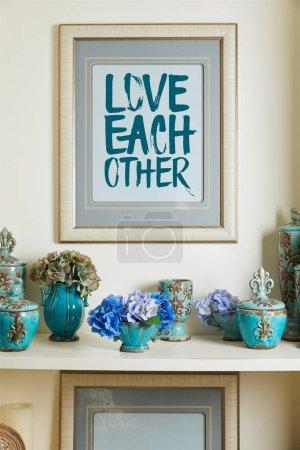 Foto de Marco de foto con amor los demás Letras y turquesa cerámica jarrones vintage adornados con flores en estante - Imagen libre de derechos