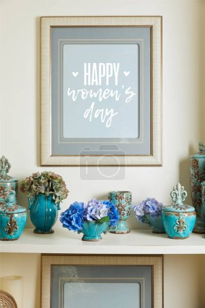 Photo for Picture frame with happy womens day lettering and turquoise ceramic ornate vintage vases with flowers on shelf - Royalty Free Image