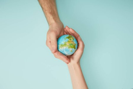 top view of man and woman holding planet model on turquoise background, earth day concept