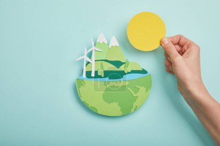 Photo for Top view of woman holding paper cut sun and planet with renewable energy sources on turquoise background, earth day concept - Royalty Free Image