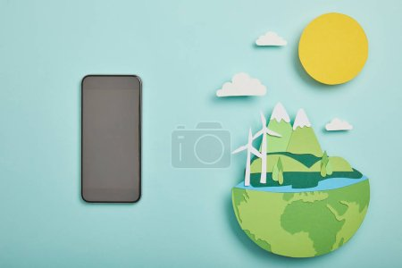top view of blank screen smartphone and paper cut planet with renewable energy sources on turquoise background, earth day concept