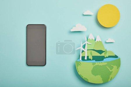 Foto de Vista superior de smartphone pantalla en blanco y papel cortado planeta con fuentes de energía renovables sobre fondo turquesa, concepto de día de la tierra - Imagen libre de derechos