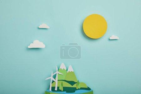Photo pour Vue de dessus du papier coupé la planète avec des sources d'énergie renouvelables sur fond turquoise, notion de jour de la terre - image libre de droit