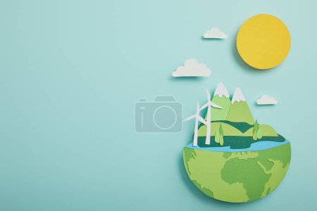 Photo for Top view of paper cut planet with renewable energy sources on turquoise background, earth day concept - Royalty Free Image