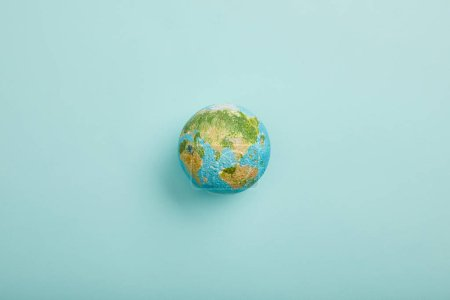 top view of planet model on turquoise background, earth day concept