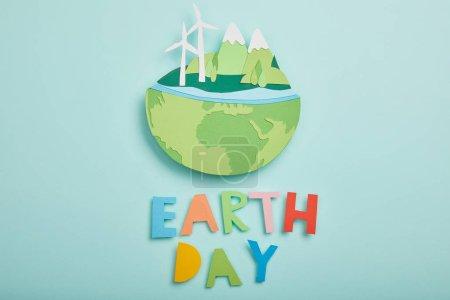 Photo pour Vue de dessus du papier coupé la planète avec des sources d'énergie renouvelables et des lettres de papier coloré sur fond turquoise, notion de jour de la terre - image libre de droit