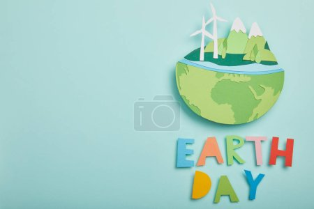 Photo for Top view of paper cut planet with renewable energy sources and colorful letters on turquoise background, earth day concept - Royalty Free Image