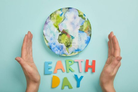 top view of woman holding colorful paper letters and planet picture on turquoise background, earth day concept