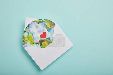 Photo pour Vue de dessus d'enveloppe avec photo de la planète sur fond turquoise, notion de jour de la terre - image libre de droit