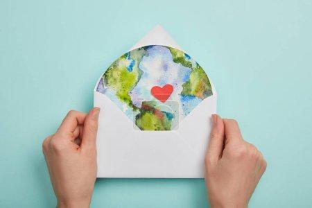Widok góry kobietę kopertę z obrazek planety na turkus tło, koncepcja dzień ziemi