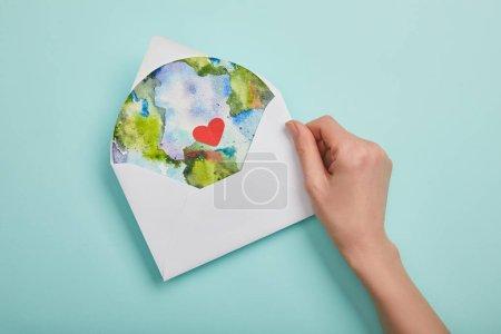 Photo pour Vue du dessus de la femme tenant enveloppe avec photo de la planète sur fond turquoise, concept de jour de la terre - image libre de droit