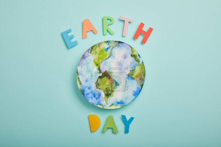 top view of colorful paper letters and planet picture on turquoise background, earth day concept