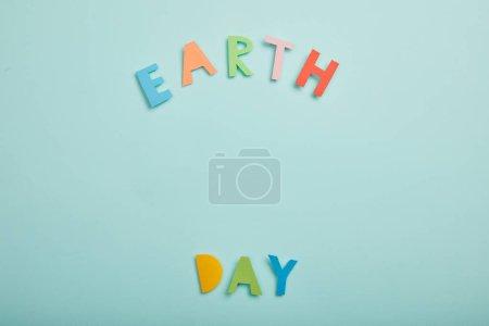 Photo pour Vue de dessus des lettres de papier coloré sur fond turquoise, notion de jour de la terre - image libre de droit