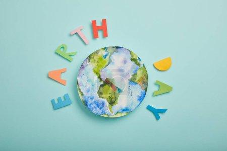 Photo pour Vue de dessus de tableau de lettres et de planète de papier coloré sur fond turquoise, notion de jour de la terre - image libre de droit