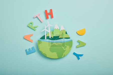 Photo for Top view of paper cut planet with renewable energy sources and colorful paper letters on turquoise background, earth day concept - Royalty Free Image