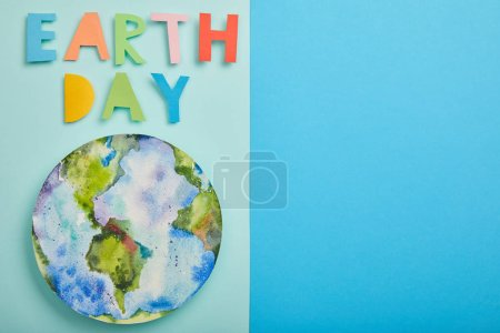 top view of colorful paper letters and planet picture on green and blue background, earth day concept