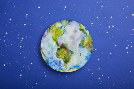 Photo for Top view of planet picture on violet background with stars, earth day concept - Royalty Free Image