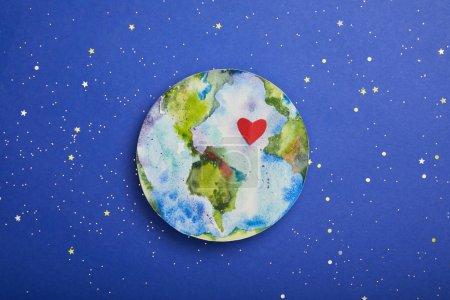 Photo pour Vue de dessus de l'image de la planète avec le symbole du coeur sur fond violet avec étoiles, notion de jour de la terre - image libre de droit