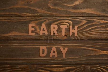 Photo pour Vue de dessus des lettres de papier sur fond en bois brun, notion de jour de la terre - image libre de droit