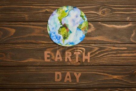 Widok z góry papieru liter i planety obrazu na brązowym tle drewnianych, koncepcja dzień ziemi