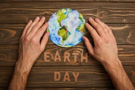 częściowy widok kobietę planet obraz i papieru liter na brązowym tle drewnianych, koncepcja dzień ziemi