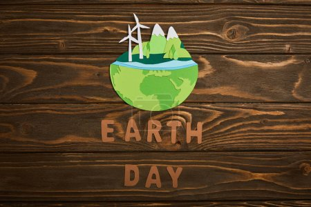 Photo for Top view of paper cut planet with renewable energy sources and letters on wooden background, earth day concept - Royalty Free Image