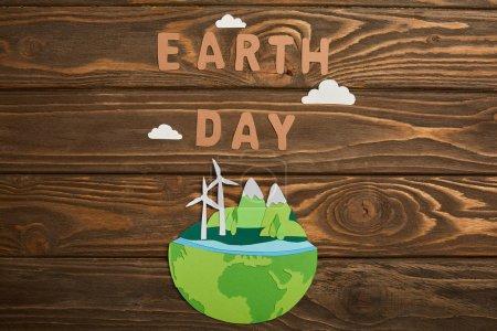 vista superior del planeta cortado en papel con fuentes de energía renovables y letras de papel sobre fondo de madera, concepto del día de la tierra