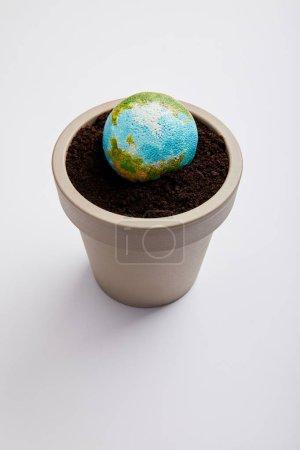 Photo pour Planète modèle placé sur pot de fleurs avec le sol, la notion de jour de la terre - image libre de droit