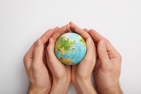 Photo pour Vue de dessus de la femme et l'homme tenant le modèle planet sur fond gris, notion de jour de la terre - image libre de droit