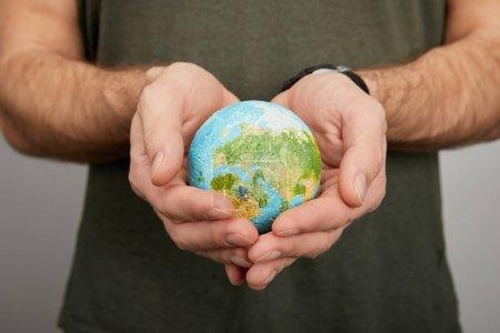Photo pour Homme tenant modèle de planète sur fond gris, concept de jour de la terre - image libre de droit