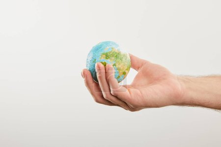 man holding planet model on grey background, earth day concept
