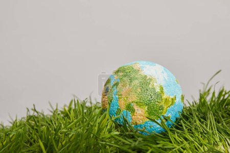 planet model placed on green grass surface, earth day concept