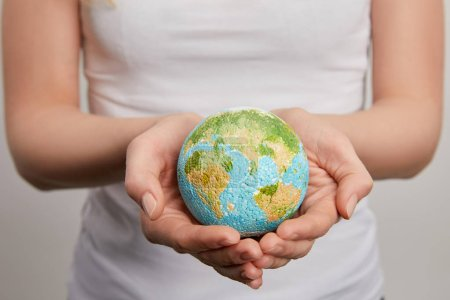woman holding planet model on grey background, earth day concept